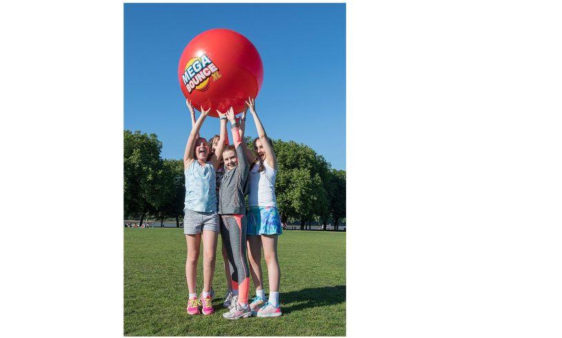 four children holding up mega bounce