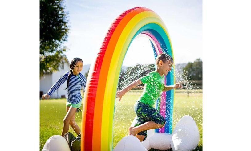 Kids run through rainbow sprinkler